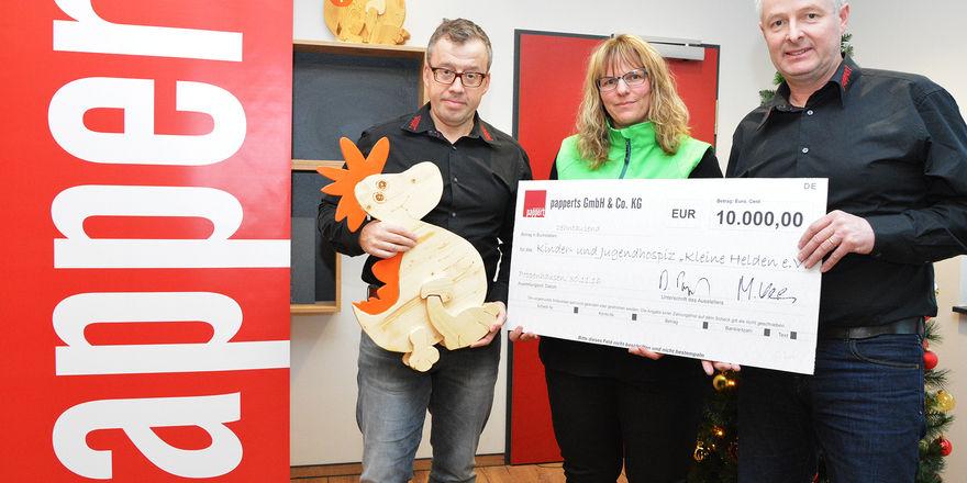 """Die Geschäftsführer der Bäckerei Pappert, Bernd Pappert (links) und Manfred Klüber (rechts), übergeben Vera Erb vom Kinderhospizverein """"Kleine Helden"""" einen Scheck im Wert von 10.000 Euro."""