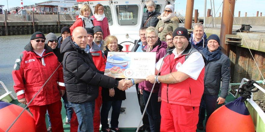 """Robert Maaßen (links) überreichte dem zweiten Vormann Christian Koprek an Bord seines Seenotrettungskreuzers """"Pidder Lüng"""" einen Spendenscheck in Höhe von 5.000 Euro."""