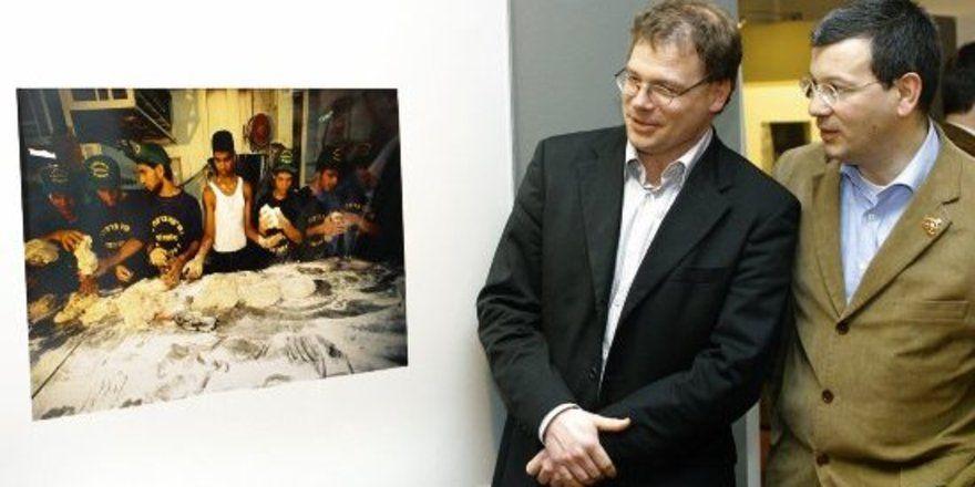 """Kurator Dr. Oliver Seifert (links) mit Museumsleiter Dr. Andrea Fadani bei der Vernissage zur Ausstellung, auf dem Foto die Abendmahlsituation """"Lehrlinge in einer Bäckerei in Jaffa""""."""