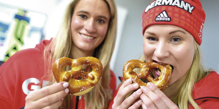 Medaillenstoff: Natalie Geisenberger (links), Olympiasiegerin im Rennrodeln, und die Zweitplatzierte Dajana Eitberger versorgen sich mit Brezeln.