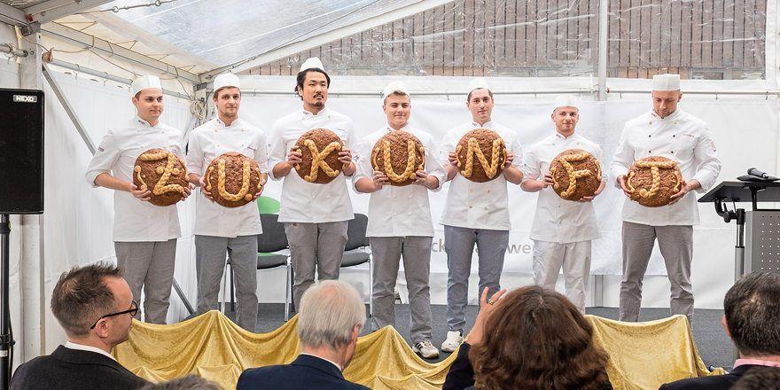 """Die Meisterschüler bei der Einweihung mit """"Zukunfts-Broten""""."""
