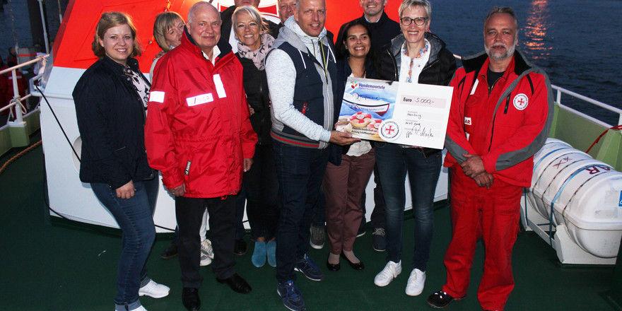 Robert Maaßen (vorne, Mitte) bei der Übergabe des Spendenschecks auf dem Seenotrettungskreuzer Berlin.