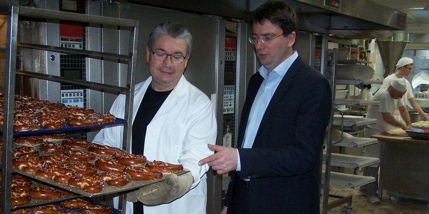 Heinz Hoffmann (links) zeigt Florian von Brunn, Verbraucherpolitischer Sprecher der SPD-Fraktion im Bayerischen Landtag, Verfahren zum Abbacken von belaugten Brezenteiglingen.