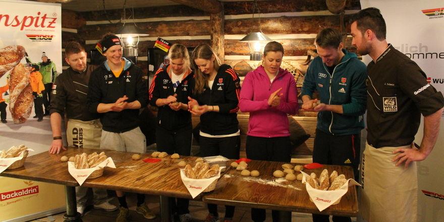 Die deutschen Sportler sind mit vollem Einsatz dabei, wenn sie unter Anleitung von Johannes Hirth (links) und Jörg Schmid (rechts) Kornspitz herstellen.