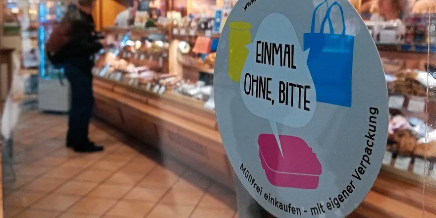 """An Geschäften der Münchner Hofpfisterei prangt schon der Sticker """"Einmal ohne, bitte"""" für verpackungsfreien Einkauf."""