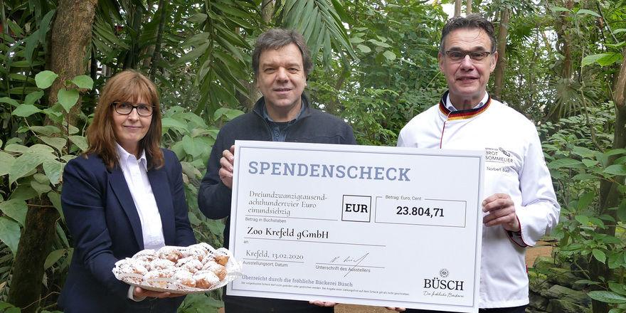 Zoo-Geschäftsführer Wolfgang Dreßen mit dem symbolischen Scheck, den ihm Norbert Büsch und Marketingleiterin Annett Swoboda auf dem Zoogelände überreichten.