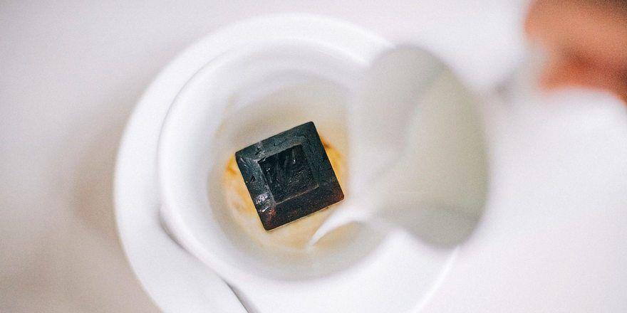 Egal ob mit Milch oder heißem Wasser: Mit einer heißen Flüssigkeit aufgegossen, wird der Espressowürfel in der Tasse zum flüssigen Kaffee.