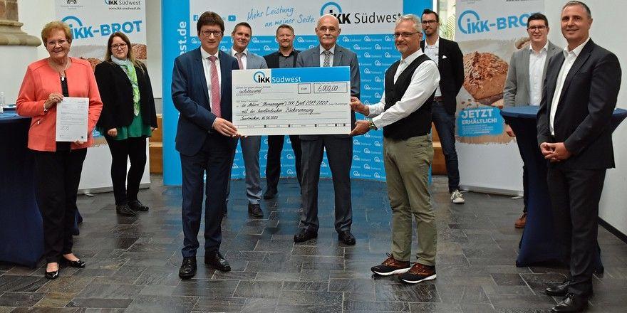 Pfarrer Wolfgang Glitt (Mitte hinten) bekommt den Spendenscheck durch die saarländische Gesundheitsministerin Monika Bachmann sowie durch IKK Südwest-Vorstand Jürgen Loth (links) überreicht.