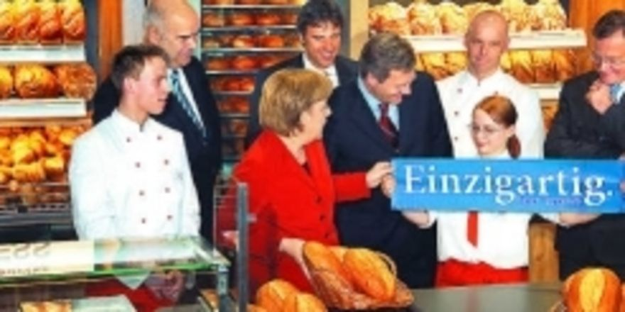 """Handwerk ist schlicht einzigartig – das entdeckten Bundeskanzlerin Angela Merkel (3. v.l.) und Niedersachsens Ministerpräsident Christian Wulff (5. v.l.) auch auf der CeBIT in Hannover. In einer Bäckerei wurde demonstriert, """"wie viel IT i"""