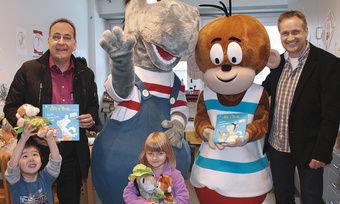 Veit-Geschäftsführer Michael Krug (links) und Armin Lang jr. freuen sich gemeinsam mit den Kindern im Olgahospital.