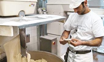 Bäckermeister Jan Asmar prüft das plastische Auskneten des Teiges für Weizenkleingebäcke, der mit Unterstützung der Eiswasseranlage (hier ohne Abdeckung) nicht wärmer als 21 °C wird.