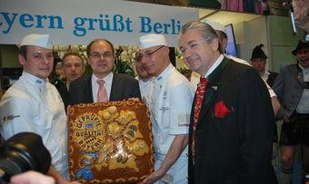 Bundesernährungsminister Christian Schmidt mit der gebackenen kulinarischen Landkarte Bayerns, Landesinnungsmeister Heinz Hoffmann (rechts) und Kollegen.