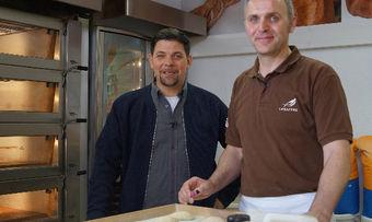 Tim Mälzer (links) lässt sich im Fala-Backstudio die Brötchenherstellung von Rico Pförtner erklären.