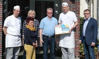 Thomas Kühnel (Zweiter von rechts) erhält den Gutschein von Bernd Wazinski, Dawn Foods (rechts). Mit dem Bäcker freuen sich die Kollegen und der Chef der Ottendorfer Mühlenbäcker GmbH.