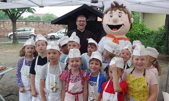 Claus Becker mit Maskottchen und begeisterten Kinder.