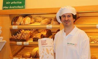 """Christian Lecht, Inhaber der Demeter-Bäckerei Backwerk aus Hannover, nimmt an der Aktion teil und zeigt hier die Tüten des """"Saat-Gut-Brotes""""."""