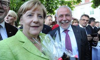 Michael Wippler, Präsident des Zentralverbands des Deutschen Bäckerhandwerks, überreicht Bundeskanzlerin Angela Merkel ein Brotpräsent.