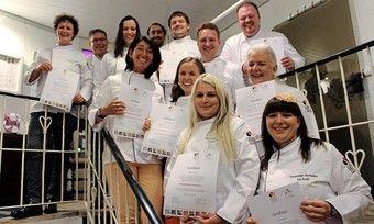 Die ersten ausgebildeten Schokoladen-Sommeliers halten stolz ihre Auszeichnungen hoch.