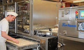 Ein Bäcker bei der Arbeit an einer Fortuna-Brötchenanlage.