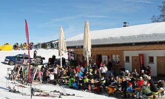 Teilnehmer und Besucher sitzen vor der Sonnenbichlhütte.