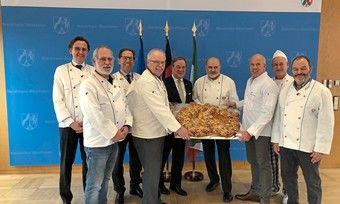 NRW-Ministerpräsident Armin Laschet (Mitte) nimmt die Neujahrsbrezel vom Vorstand des Verbandes des Rheinischen Bäckerhandwerks entgegen.