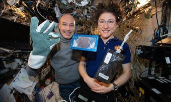 Die Astronauten Luca Parmitano und Christina Koch mit Milch und dem im All gebackenen Keks.