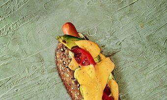 Vegetarisch: Die Veggie-Würstchen im Mehrkorn-Baguettebrötchen sind mit Avocado sowie Tomaten kombiniert und mit Käse überbacken.